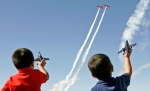 From left, Zaniel Payen, age 4, and Emanuel Duran, age 5, watch a performance by the AeroShell Aerobatic Team during AirSho 2012 Saturday, Oct. 13 at Midland International Airport.
