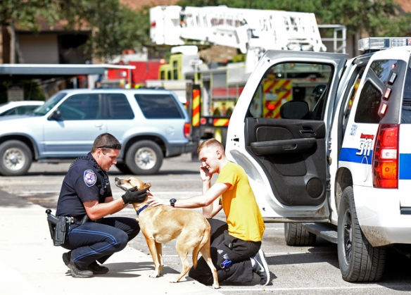 Midland Police Department officer Tyler Thompson returns a dog named Leo to his owner, Austen Lawler, after the animal was rescued by Midland firefighters from an apartment fire at The Annex apartments on Friday, Oct. 16, 2015. James Durbin/Reporter-Telegram