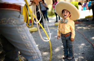 Alfredo Grimaldo, Jr., age 2, watches his father practice traditional charro rope twirling during the Hispanic Cultural Center of Midland's annual Cinco de Mayo celebration on Thursday, May 6, 2016, at Hogan Park. James Durbin/Reporter-Telegram