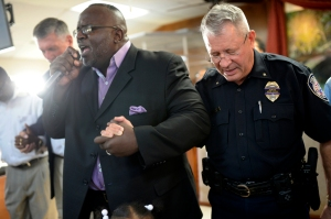 Pastor Tommie Hale prays while holding hands with Midland Police Department Deputy Chief Jeff Darr during a prayer service for love and peace Wednesday, July 13, 2016, at Mount Calvary Missionary Baptist as the nation mourns the deaths of citizens in police custody and five Dallas law enforcement officers killed in a retaliatory attack.