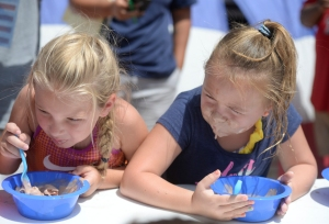 Krista Law, age 5, and Abigail Lindsey, age 6, compete in an ice cream eating contest during an Ice Cream Festival hosted by Do 432 featuring inflatable water slides from Tiki Island Waterpark, Saturday, July 30, 2016, in a parking lot near S. Big Spring Street and W. Kentucky Ave.
