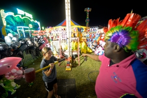 DeJay Evans gives Mica Henley, age 11, some advice on how to swing the hammer during the St. Ann's carnival Thursday, Sept. 22, 2016.