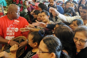 Donnell Allen, a sales associate at JCPenny, attempts to hand out coupon packets while being rushed by a crowd of Black Friday shoppers shortly after the doors opened at 3 p.m. on Thursday, Nov. 24, 2016, at Midland Park Mall. James Durbin/Reporter-Telegram